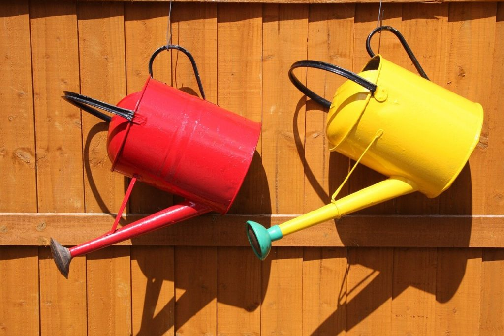 use a watering can for potted plants or areas of your yard that you want to give special attention